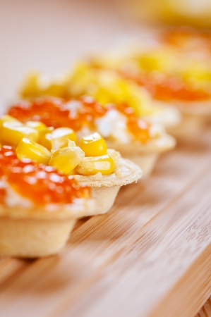 Tartlets with red caviar and corn on wooden table. photo