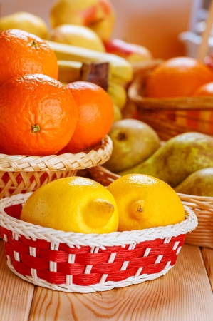 Lemons, oranges, pears and apples in baskets on wooden table. Stock Photo - 16378114