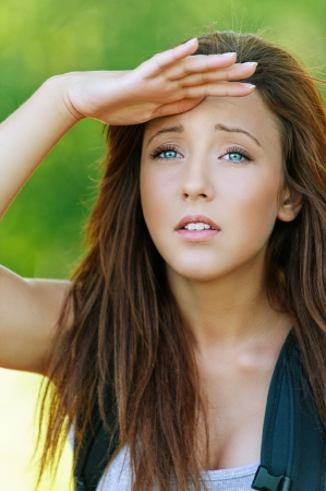 Beautiful young woman with hand closes eyes from sun and looks into distance, against background of summer green park. Stock Photo - 16367574