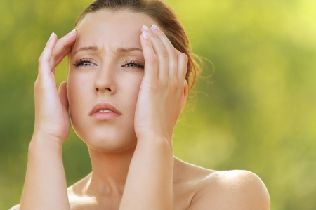 Beautiful young woman holding head in pain, against background of summer green park. Stock Photo - 16367584