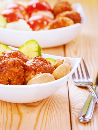 Meatballs and mushrooms in white plate on wooden table  photo
