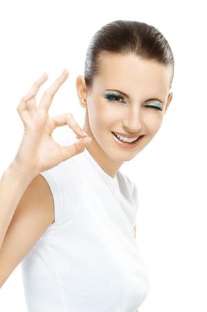 Mooie glimlachende donkerharige vrouw in witte T-shirt met vooraan ondertekenen OK, close-up, geïsoleerd op witte achtergrond.