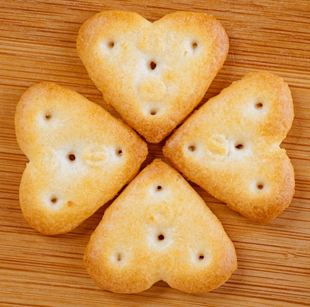 puff pastry: Four heart-shaped cookies, lined pattern on wooden table. Stock Photo