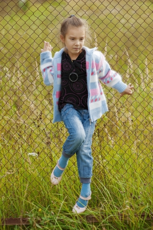 Beautiful little girl on metal grid in old grassy park  photo