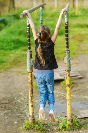 Beautiful little girl hanging on old exercise equipment in deserted park  Stock Photo - 16639239