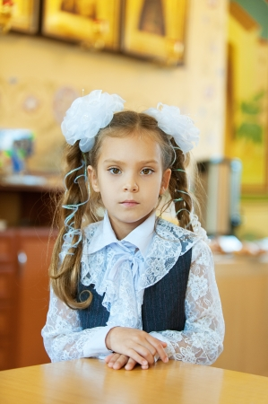Beautiful little girl with big white bows around table Stock Photo - 16639232