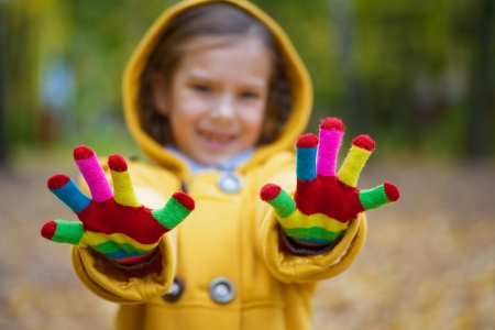 Beautiful smiling little girl shows colored woolen gloves in yellow autumn park Stock Photo - 16639235