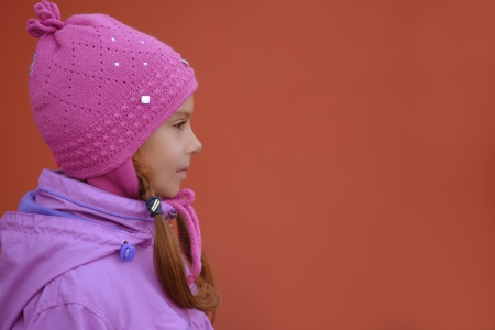 Beautiful little girl in pink jacket and hat of profile on red background Stock Photo - 16639234