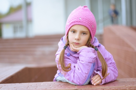 pink hat: Beautiful little girl in pink hat and jacket around school building