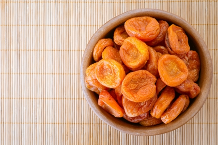 Wooden plate with dried apricots, on beige bamboo tablecloth Stock Photo - 16694274