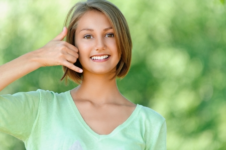 Smiling beautiful young woman talking on phone simulates, against background of summer green park. photo