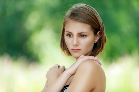 Portrait of pensive beautiful young woman, against background of summer green park. Stock Photo - 16685969