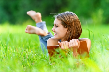 Smiling beautiful young woman lying on grass and reading book, against background of summer green park. Stock Photo