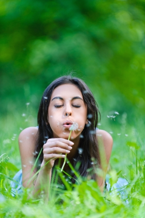 girl blowing: Beautiful dark-haired young woman lying on grass and blows away dandelion, against background of summer green park. Stock Photo