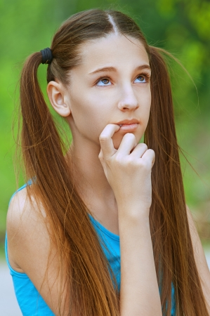 teen girl face: Beautiful smiling teenage girl in blue shirt thoughtfully looking up, against background of summer green park. Stock Photo