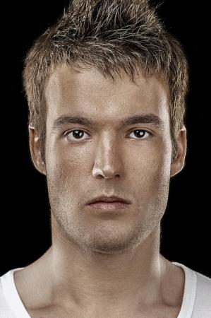 close up: Brutal portrait of young man close up on black background.