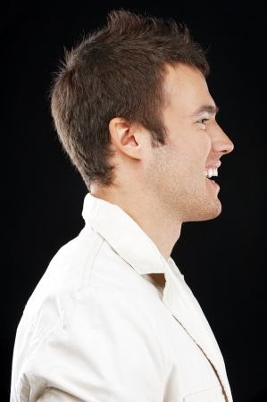 european expression face: Portrait of young handsome man in profile close up on black background. Stock Photo