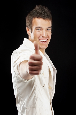 ok hand: Young handsome man raises up thumb, on black background.