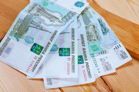 roubles: Five thousand banknotes of rubles on wooden table. Stock Photo