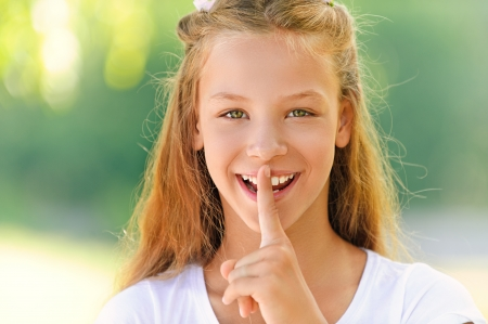 Young beautiful girl puts forefinger to lips. photo