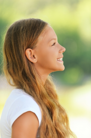 preteen model: Portrait of young beautiful smiling girl in profile, against green summer garden.