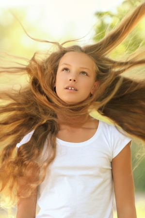 Young beautiful girl with hair that wind is blowing, against green summer garden. photo