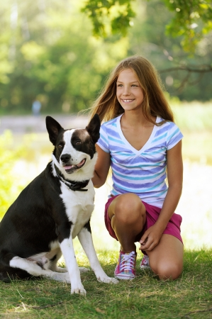 Jonge mooie glimlachende meisje met zwarte hond, tegen groene zomer tuin.