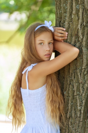 huge: Young beautiful smiling girl near large tree, against green summer garden. Stock Photo