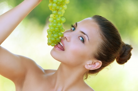 viands: Beautiful young woman bites off from grape bunches, against summer green park.