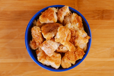 nuggets: Chicken nuggets in blue plate on wooden table.