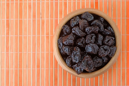 Dried prunes in wooden bowl on orange bamboo table cloth. photo