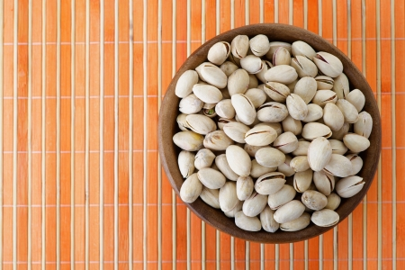 Salted peanuts in wooden bowl on orange bamboo tablecloth. photo