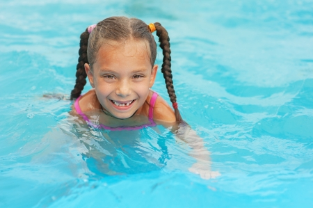 Pretty smiling little girl swims in childrens pool. photo