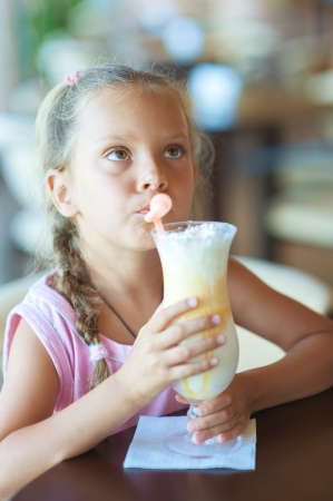 Pretty little girl drinking milkshake at restaurant. photo