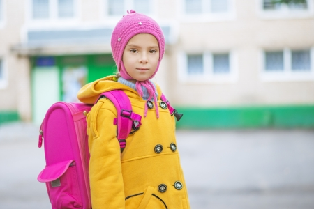 bookbag: Beautiful little girl in yellow coat and pink knapsack goes to school. Stock Photo