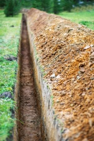 Lange aarden geul gegraven worden om pijp.