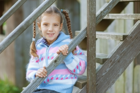 Little beautiful smiling girl sitting on wooden stairs of playground  photo