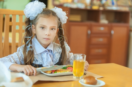 mealtime: Little beautiful girl with big white bows sitting at table having dinner  Stock Photo