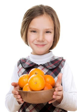 Little smiling pretty girl holding bowl of ripe oranges, isolated on white background Stock Photo - 17592829