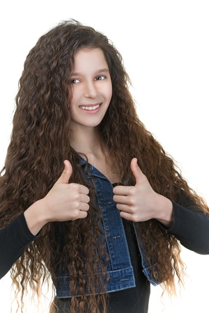 Beautiful smiling schoolgirl with dark curly hair raises thumbs-up, isolated on white background. photo