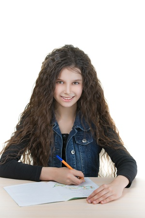 life jackets: Beautiful smiling schoolgirl with dark curly hair sitting at table and wrote in notebook, isolated on white background. Stock Photo