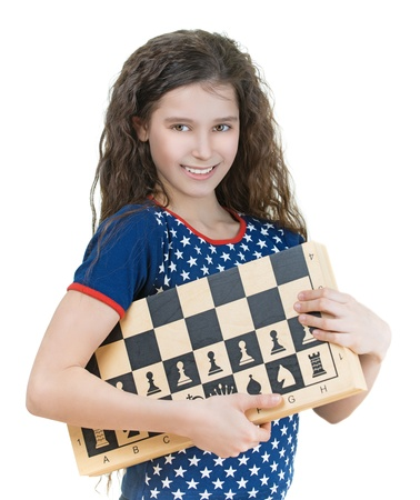 Portrait of beautiful smiling schoolgirl with dark curly hair and chess board, isolated on white background. photo