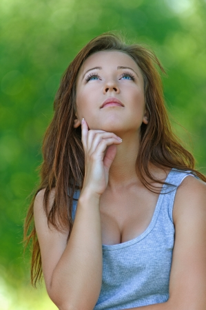 Portrait of beautiful attractive young sad woman has reflected on life at summer green park Stock Photo - 17850036