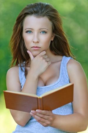 earnest: Retrato de la atractiva chica lectura libro serio, vestido con camiseta gris a verde de verano del parque. Foto de archivo
