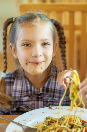 bedraggled: Beautiful smiling little girl with stained face eating pasta at restaurant