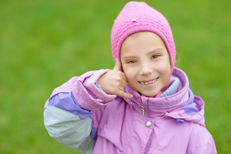 Beautiful smiling little girl in pink jacket simulates talking on cell phone  photo
