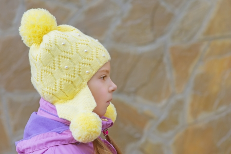 Beautiful little girl in pink jacket and yellow cap close-up in profile against a stone wall  Stock Photo - 18181255