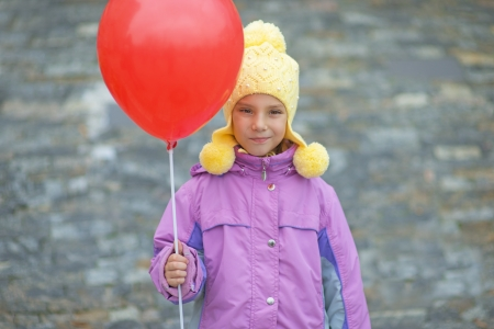 Beautiful smiling little girl in pink jacket with red balloon  Stock Photo - 18181253