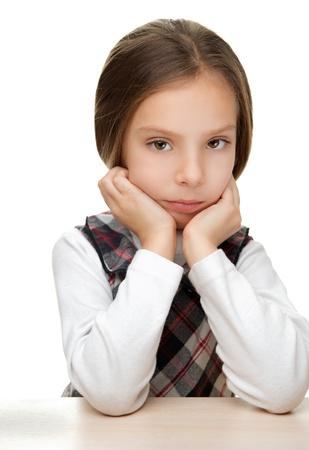 petite fille triste: Belle petite fille triste assis à la table, isolé sur fond blanc Banque d'images