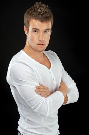 manly man: Portrait of young man in white shirt, isolated on black background.
